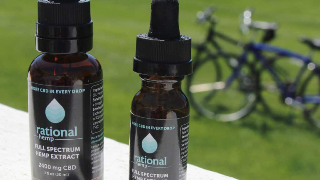 CBD oil bottles from Rational Hemp outdoors, in front of a pair of bikes